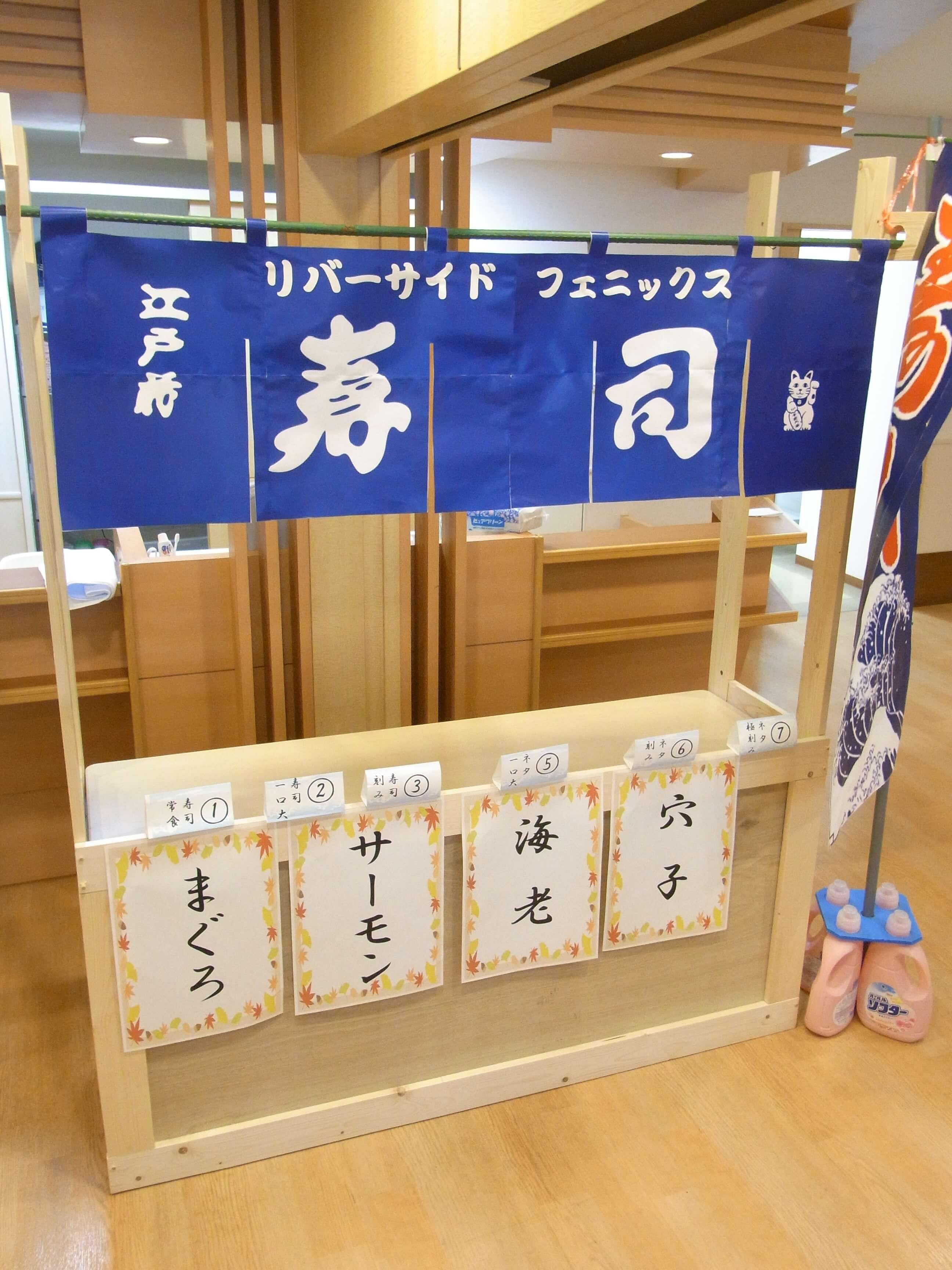 手作りの屋台やのぼりを準備し、寿司屋の雰囲気を演出しました。