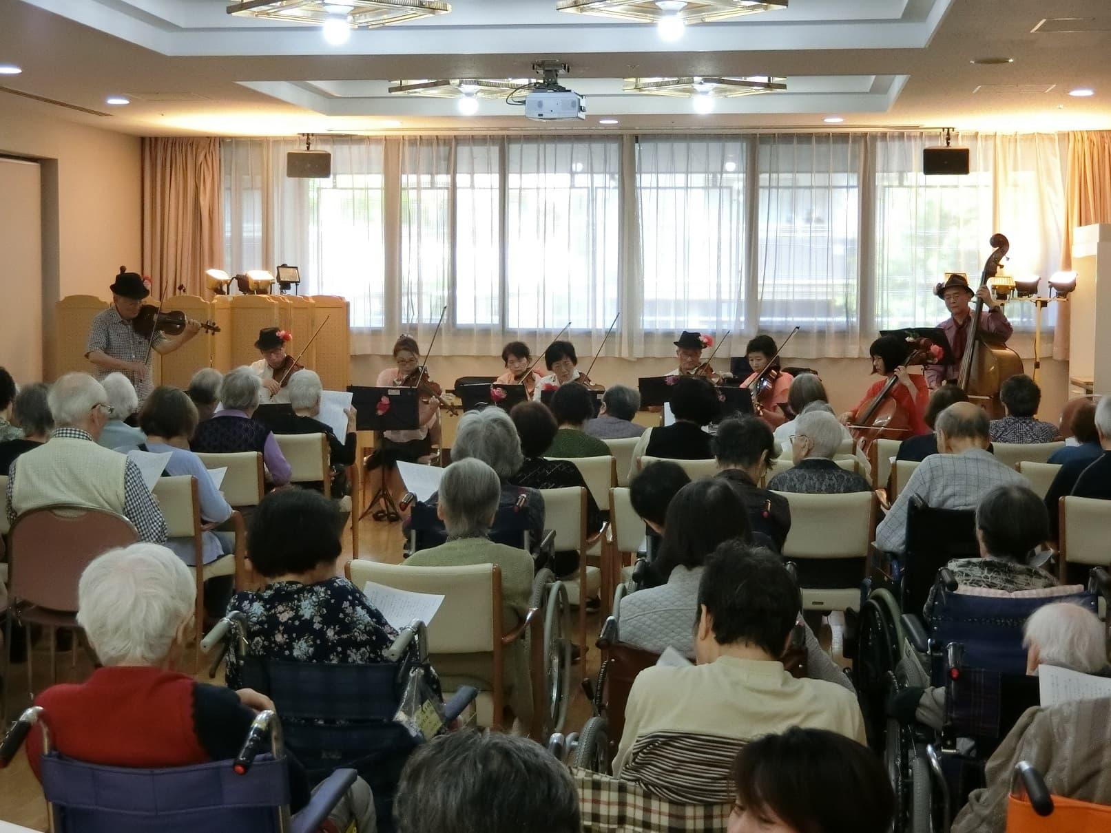 多くのご利用者の方々が会場に集まり、生演奏に感動されました。 また、楽団の伴奏に合わせて皆さんで一緒に合唱するコーナーもご用意いただき、会場は大変盛り上がりました。