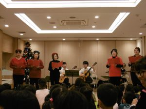 ギターの伴奏で先生たちが歌います。今年話題のパプリカが始まるとこどもたちは立ち上がって一斉に踊り出します。